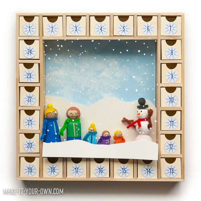 Create your own ADVENT CALENDAR with this snowy scene with your family portrait and a snowman! (Made of peg people and beads). This makes a beautiful, handmade holiday gift! We provide you with ideas for what to include in your countdown to Christmas as well.
